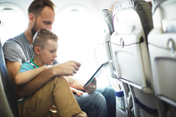 Father and son travelling in plane stock photo