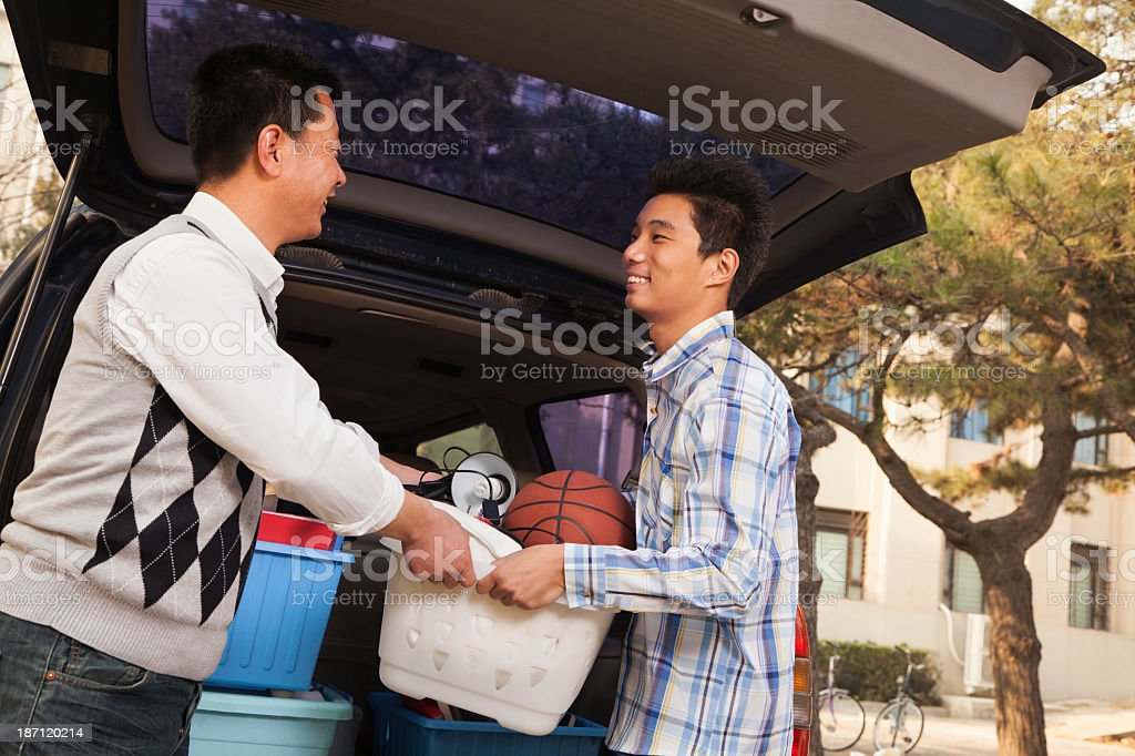 A father and son unpacking their car for college move in royalty-free stock photo