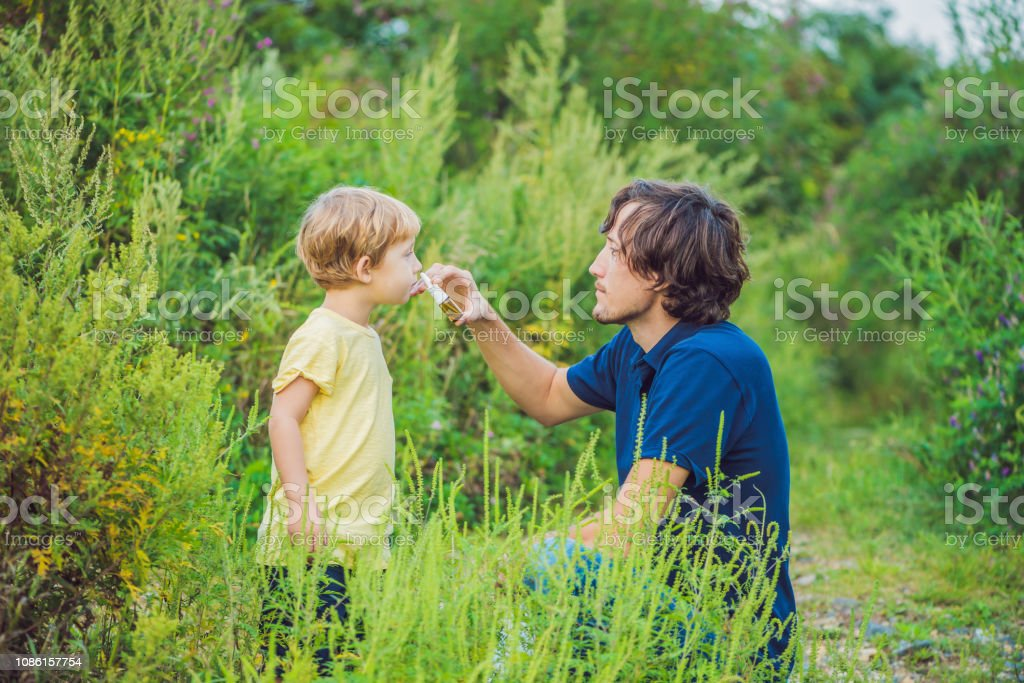 Father and son use a spray from an allergy because of an allergy to...