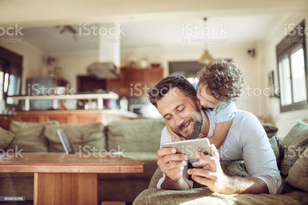Father and son using a phone stock photo