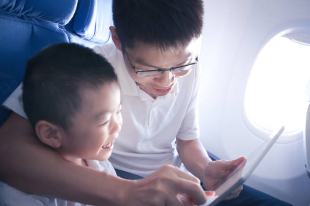 Father and son using digital tablet in airplane stock photo