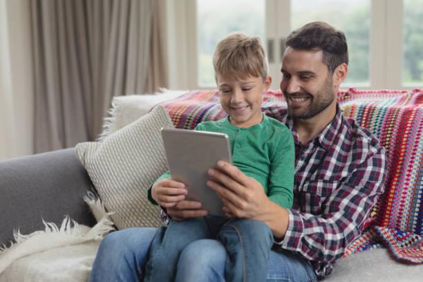 Vater und Sohn mit digitalen Tablet auf dem Sofa in einem komfortablen Haus – Foto