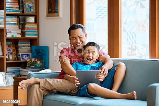 Father and son using digital tablet on sofa. Mid adult man with boy holding wireless computer in living room. They are wearing casuals at home.