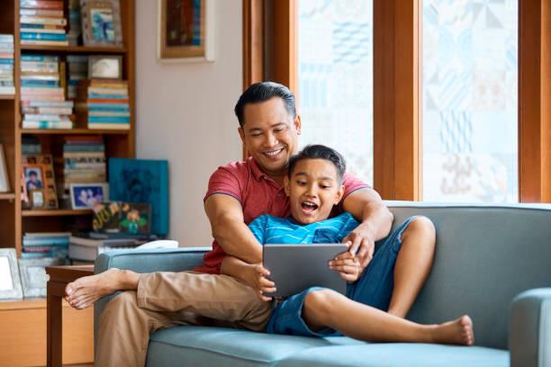 pai e filho usando tablet digital no sofá - malásia - fotografias e filmes do acervo