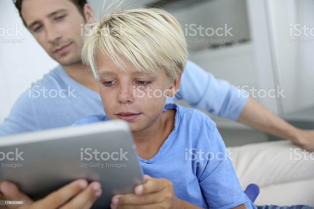 Father and son using digital tablet stock photo
