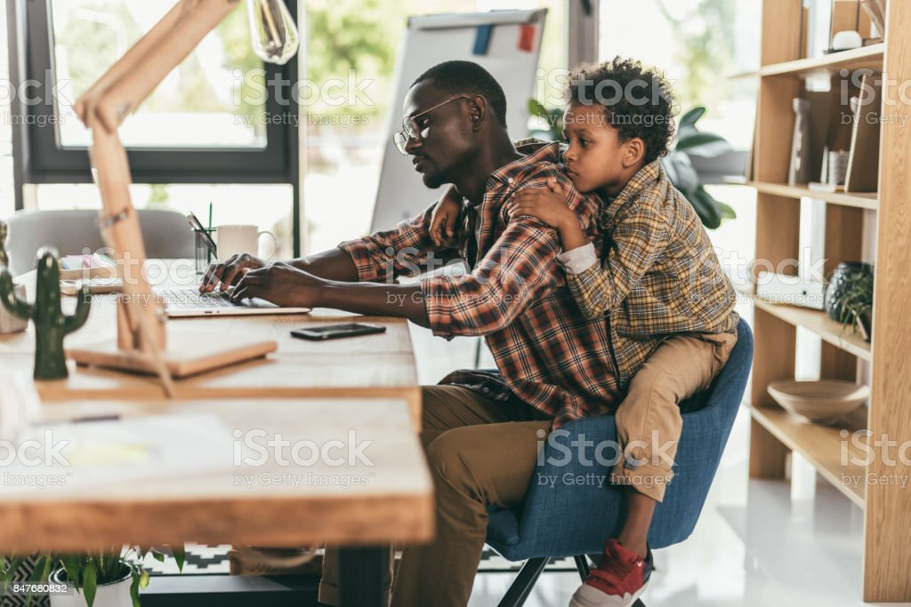 father and son using laptop in office - foto stock