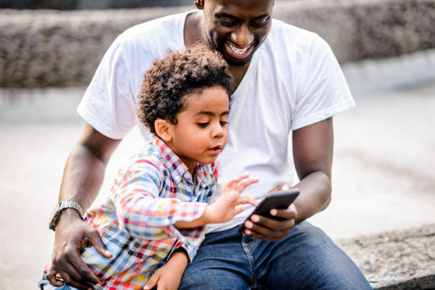 Father and son using mobile phone stock photo