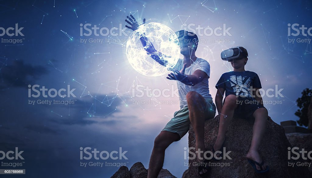 Father and son using Virtual Reality glasses sitting outside stock photo