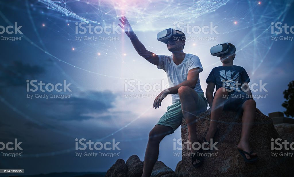 Father and son using Virtual Reality glasses sitting outside - foto de stock