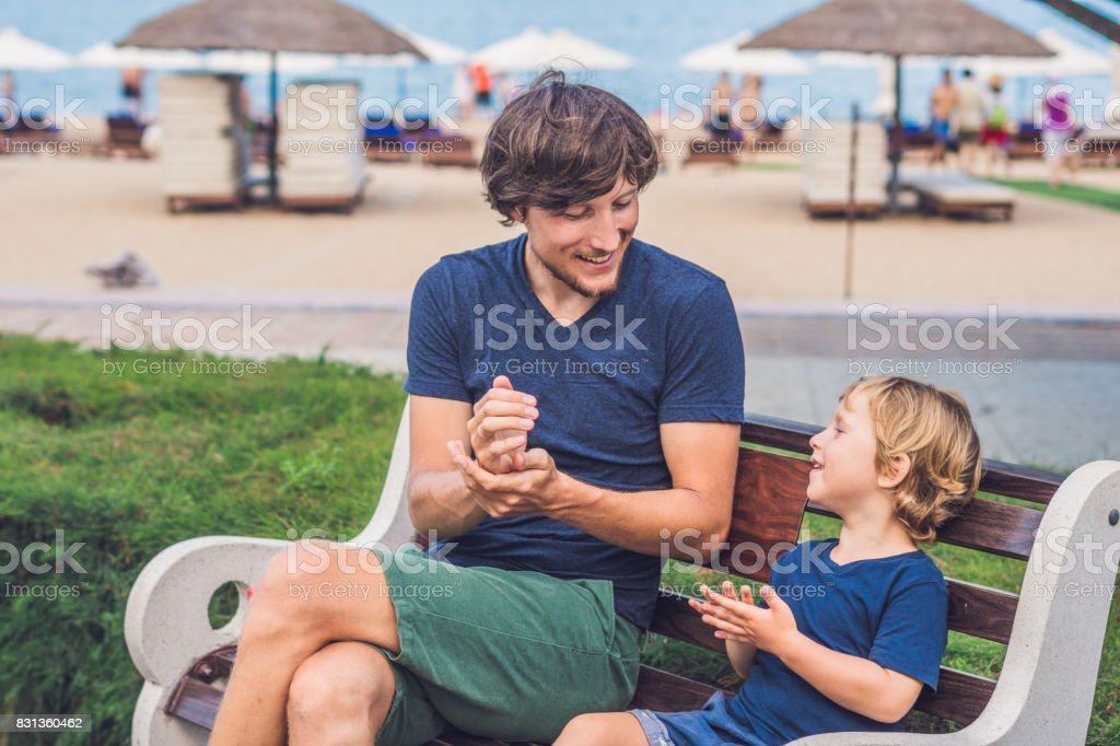 Father and son using wash hand sanitizer gel stock photo