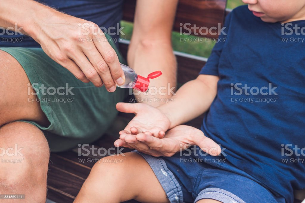 Father and son using wash hand sanitizer gel pump dispenser stock photo