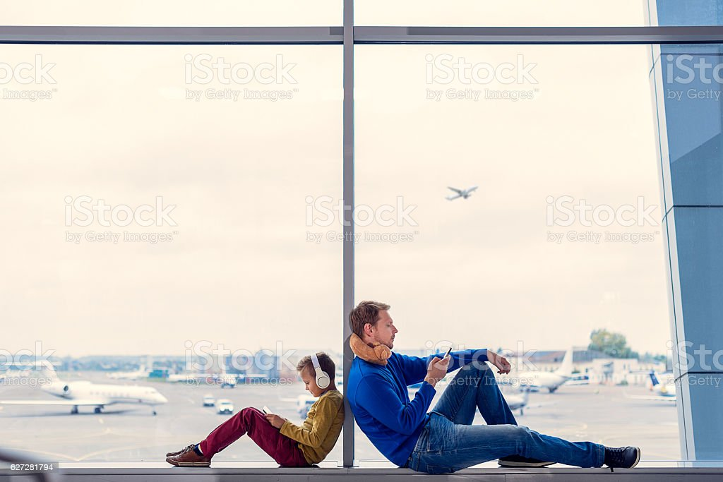 Father and son waiting to board in airport stock photo