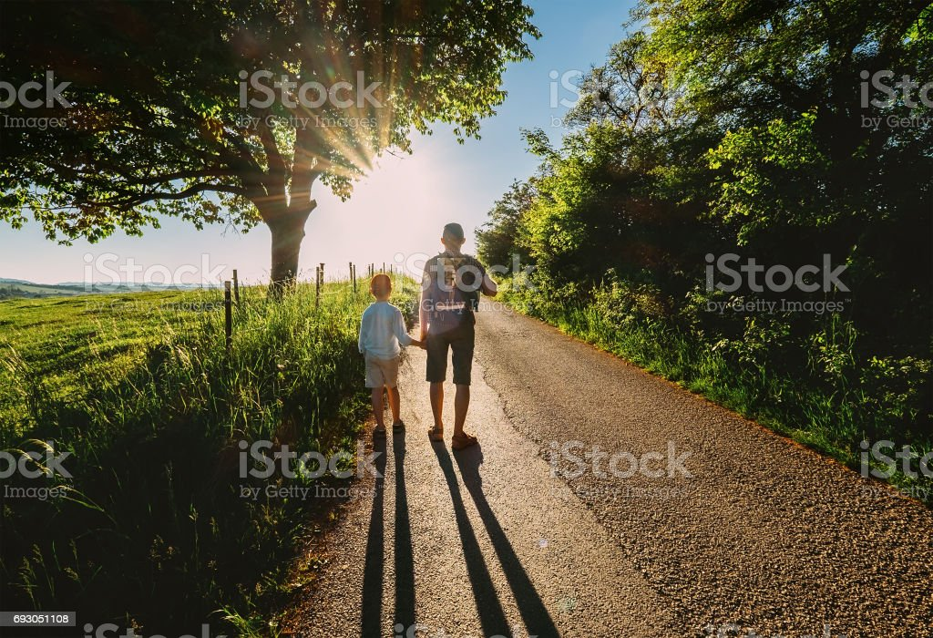 Father and son walk on sunset road stock photo