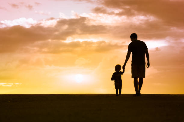 Father and son walking at sunset stock photo