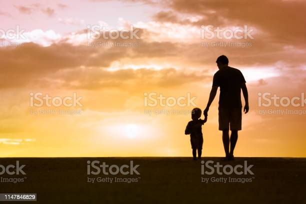 Photo of Father and son walking at sunset