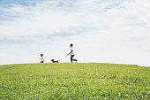 公園で一緒に犬を歩く父と息子