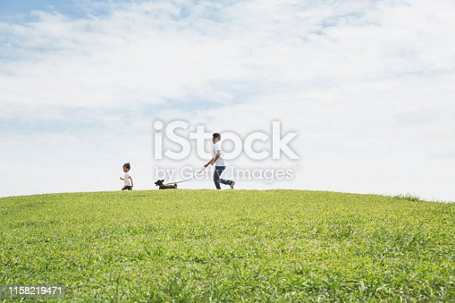 Asian man and boy with toy poodle playing outdoors.