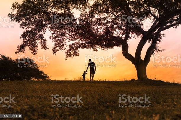 Photo of Father and son walking in the park