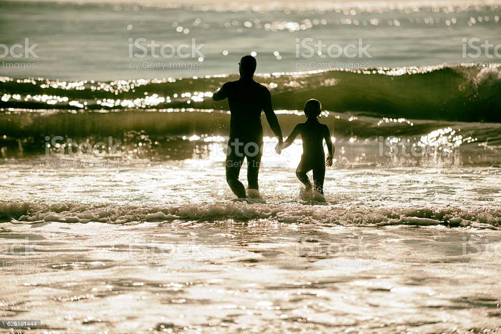 Father and son walking into surf in beautiful warm light stock photo