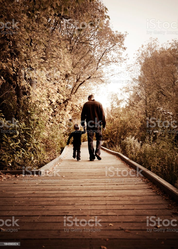 Father and Son Walking on Board Walk stock photo
