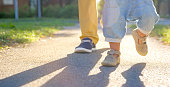 Low section of father and son walking on road in park.