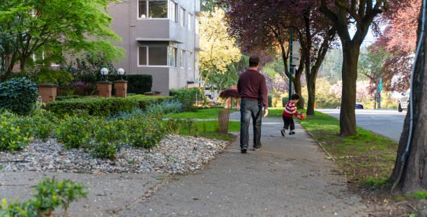 Vater und Sohn spazieren in der ruhigen Stadtstraße in Vancouver, BC, Kanada. – Foto
