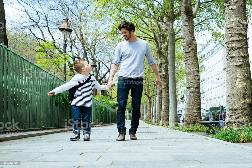 Father And Son Walking Through The Park, Going To School stock photo