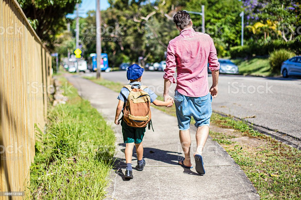 Father and son walking to school stock photo