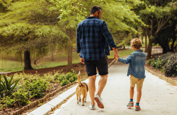 father and son walking with a dog in the park - bambino cane foto e immagini stock