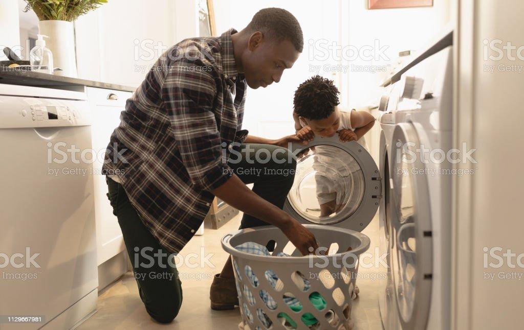 Vader en zoon kleren wassen in de wasmachine - Royalty-free 30-34 jaar Stockfoto