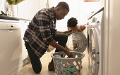 African American father and son washing clothes in washing machine at home