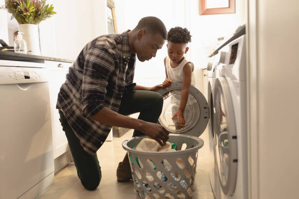 Father and son washing clothes in washing machine African American father and son washing clothes in washing machine at home single father stock pictures, royalty-free photos & images