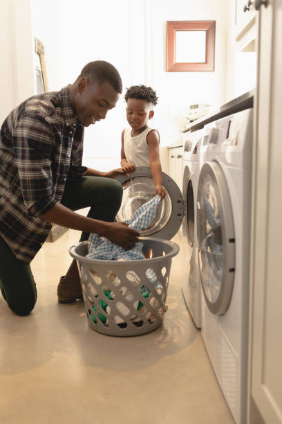 Father and son washing clothes in washing machine stock photo