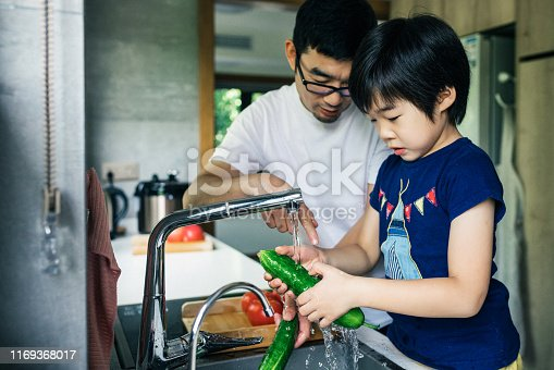 Cute child washing tomatoes and cucumbers.