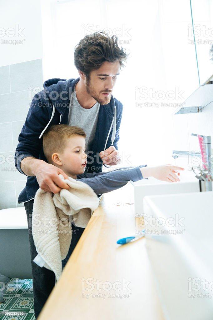 Pai e filho de lavagem de mãos foto royalty-free