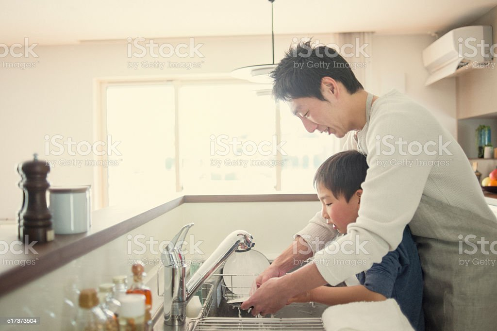 Father and son washing the dishes together in the kitchen stock photo