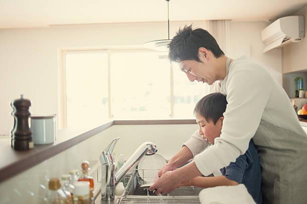 キッチンで皿を洗う父と息子 - 家事 ストックフォトと画像