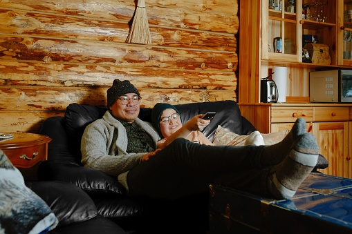 Father and son watch TV together in cabin located in rural Alberta