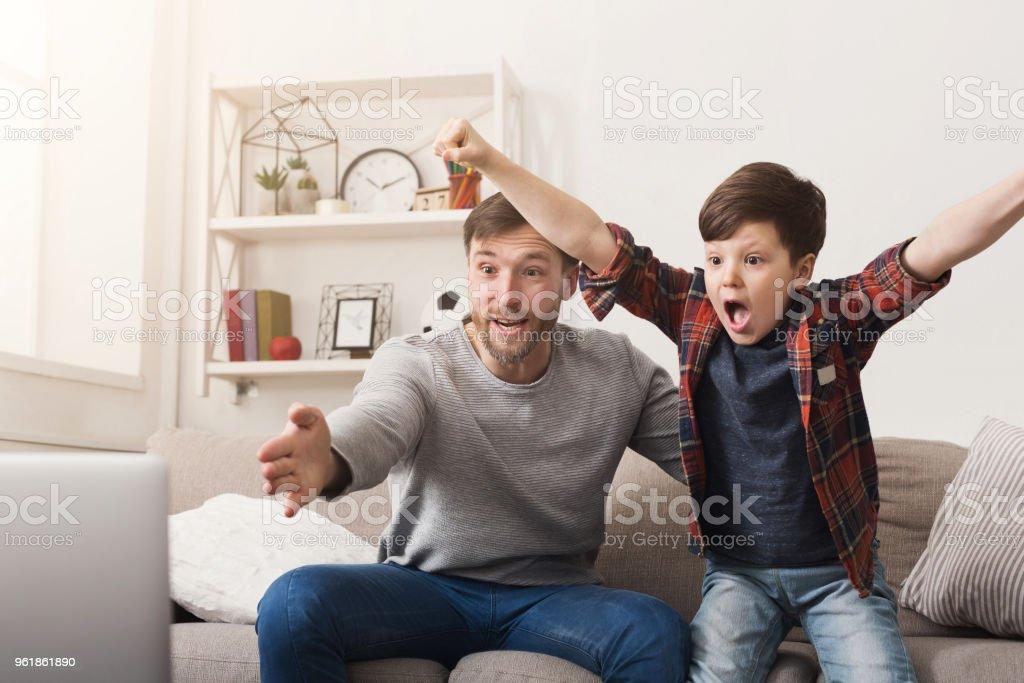 Pai e filho assistindo futebol na TV em casa - foto de acervo