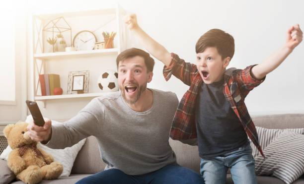 padre e hijo viendo fútbol en la televisión en casa. - family watching tv fotografías e imágenes de stock