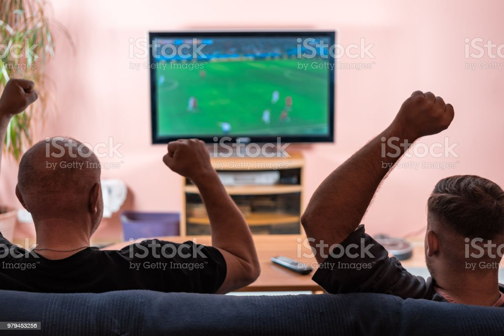 Father and son watching football or soccer on a TV. stock photo