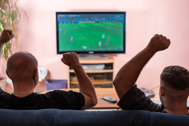 vater und sohn gerade fußball- oder fußball auf einem fernsehgerät. - fußball themenzimmer stock-fotos und bilder