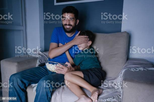 Padre e hijo viendo scary movie en la tv por la noche. Padre que cubre los ojos de su hijo - Foto de stock de Adulto libre de derechos