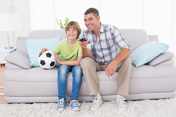 Father and son watching soccer match on sofa stock photo
