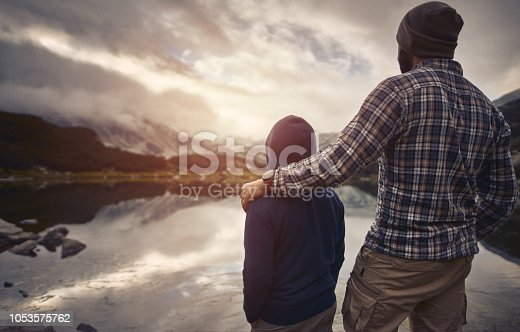 Father and son watching sunset in the montains. Pirin National Park, Bulgaria