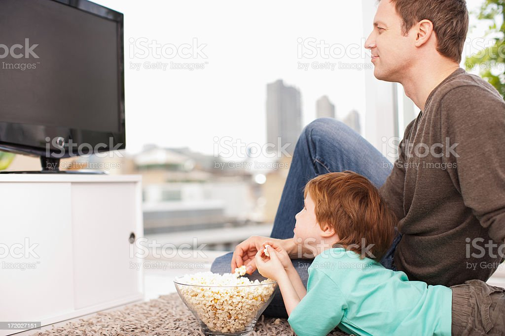 Father and son watching television stock photo
