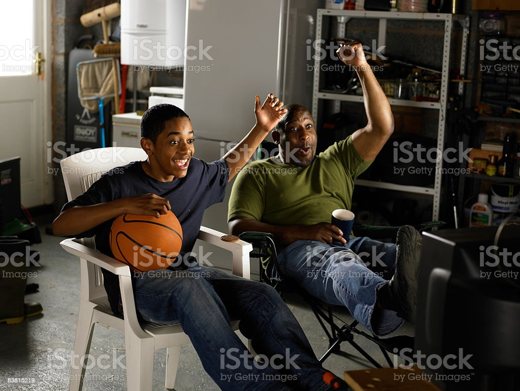 Father and Son watching TV and celebrating  royalty free stockfoto
