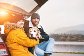 istock Father and son with beagle dog siting together in car trunk and smiling into camera. 1070307142