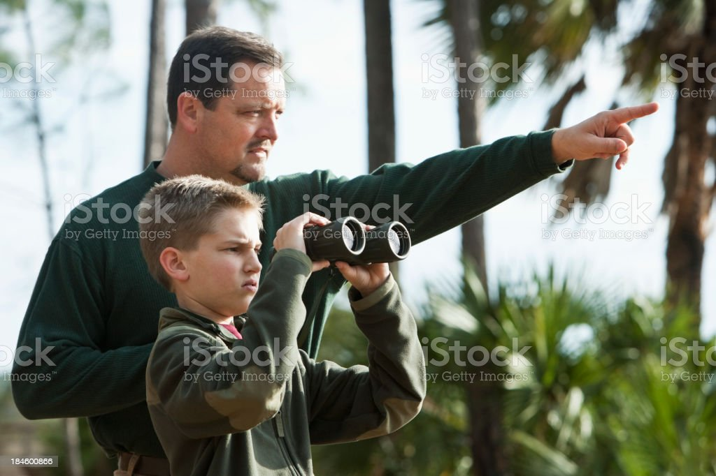 Father and son with binoculars, looking into distance royalty-free stock photo