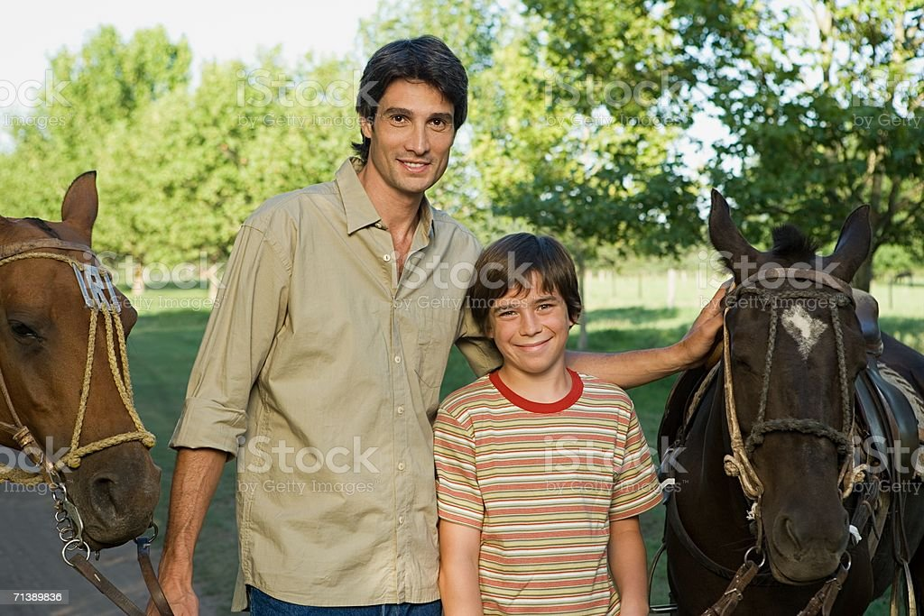 Father and son with horses royalty-free stock photo